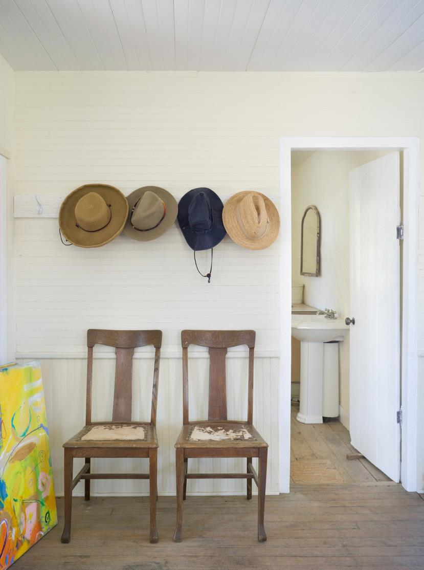 Wall-mounted-hooks-over-a-pair-of-entryway-chairs
